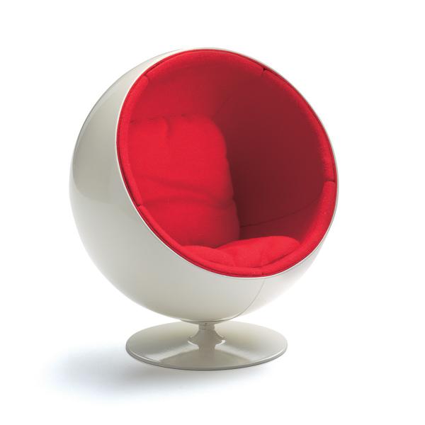 ball chair eero aarnio, 1965 vitra miniatures collection - In seiner einfachen, prägnanten Form und der signalhaften Farbigkeit ist Eero Aarnios Ball Chair ein typisches Symbol für die optimistische, konsumorientierte Populärkultur der 60er Jahre. Auch eine zeittypische, unverhohlene Begeisterung für das Technische wird deutlich: im exponierten Kunststoff, mit dem damals ganz neu selbst komplexe Formen relativ einfach in Serie produziert werden konnten, wie auch in der dynamischen Form, die an eine Raumkapsel erinnert. Die Idee einer solchen beweglichen Kapsel als Aufenthaltsort innerhalb des Hauses nimmt aber auch schon Wohnkonzepte vorweg, wie sie in den 70er Jahren für eine junge, liberale Gesellschaft diskutiert wurden. Während die glänzend polierte Kugel nach außen futuristisch und kühl wirkt, verbirgt sich im Inneren ein abgeschirmter, gemütlicher Erlebnisraum. Geräusche von außen dringen nur sehr gedämpft ins Innere, wo man sich in vielerlei Positionen, etwa im Schneidersitz, komfortabel aufhalten kann. Dicht über dem Boden auf einen runden Metallfuß montiert, läßt sich die Kugel komplett um die eigene Achse drehen und damit der Ausblick aus der »Höhle« variieren. So steht der Ball Chair für eine besondere Kategorie häuslicher Objekte. Sie ist angesiedelt zwischen Möbel und Architektur und verkörpert Mobilität und Sesshaftigkeit zugleich.